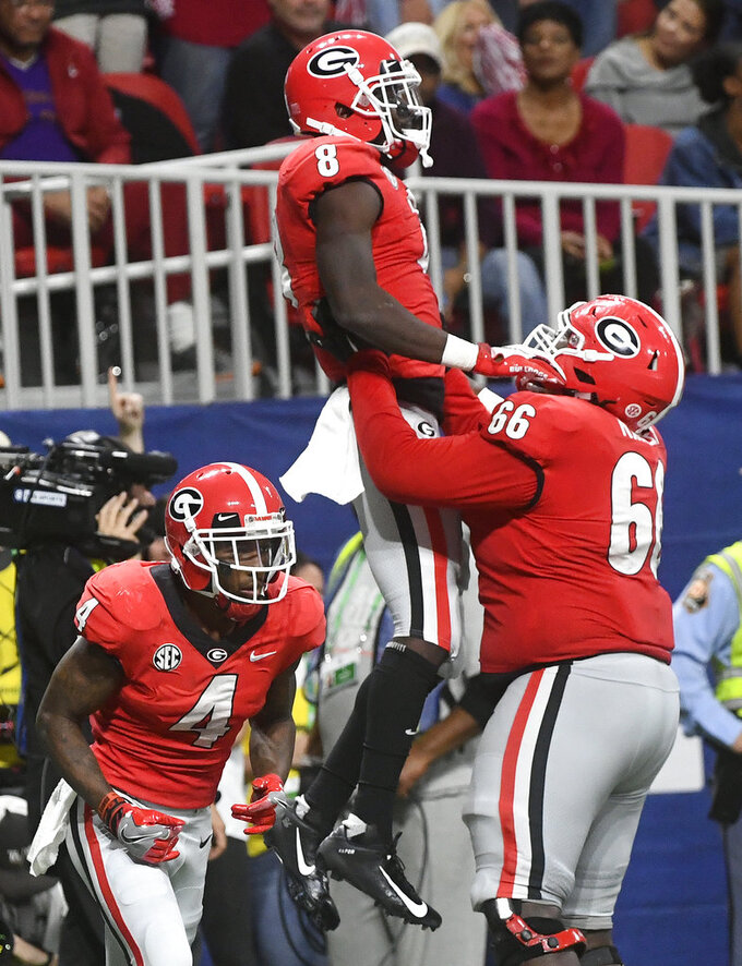 Georgia wide receiver Riley Ridley (8) is hoisted in the air by Georgia offensive lineman Solomon Kindley (66) after Ridley scored a touchdown against Alabama during the second half of the Southeastern Conference championship NCAA college football game, Saturday, Dec. 1, 2018, in Atlanta. (AP Photo/John Amis)