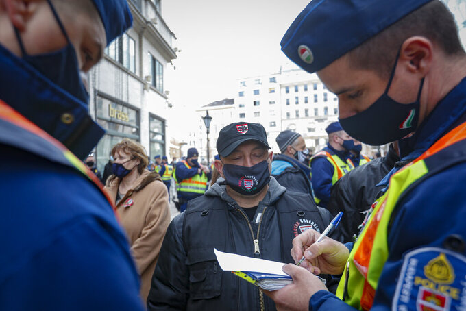A policeman writes down the identification details of a man during a protest in Budapest, Hungary, Monday, March 15, 2021. Hungarians gathered on the country's national day to protest against the current lockdown measures after new restrictive measures were introduced by the Hungarian government last week aiming to slow a record-breaking wave of COVID-19 hospitalizations and deaths. (AP Photo/Laszlo Balogh)
