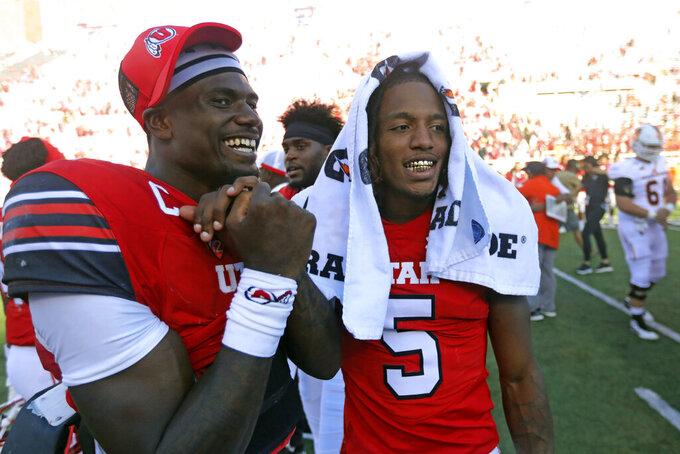 Utah quarterback Tyler Huntley , left, celebrates with teammate defensive back Tareke Lewis (5) following their NCAA college football game against Idaho State Saturday, Sept. 14, 2019, in Salt Lake City. (AP Photo/Rick Bowmer)