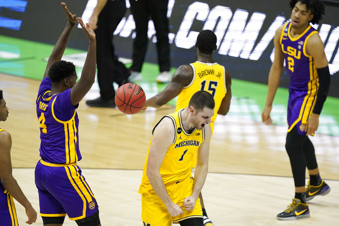 Michigan center Hunter Dickinson (1) celebrates in front of LSU forward Darius Days (4) after making a basket during the first half of a second-round game in the NCAA men's college basketball tournament at Lucas Oil Stadium Monday, March 22, 2021, in Indianapolis. (AP Photo/Darron Cummings)