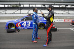 Bubba Wallace, left, and Corey LaJoie talk before a NASCAR Cup Series auto race at Indianapolis Motor Speedway in Indianapolis, Sunday, July 5, 2020. (AP Photo/Darron Cummings)
