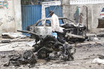 A security officer checks the wreckage after a car bomb attack at a Presidential Palace checkpoint in Mogadishu, Somalia, Saturday Sept. 25, 2021. Police said a vehicle laden with explosives rammed into cars and trucks at a checkpoint leading to the entrance of the Presidential Palace, killing at least eight people. (AP Photo/Farah Abdi Warsameh)