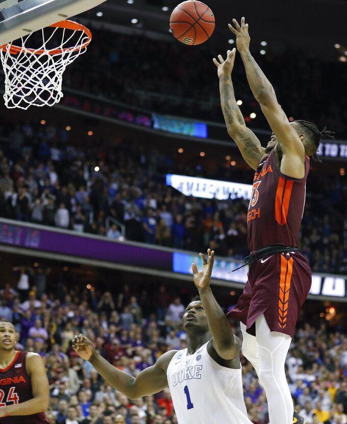 Virginia Tech guard Ahmed Hill (13) jumps for ball on his way to the basket in the final seconds, over Duke forward Zion Williamson (1) in an NCAA men's college basketball tournament East Region semifinal  in Washington, Friday, March 29, 2019. Hill missed the layup. Duke won 75-73. (AP Photo/Patrick Semansky)