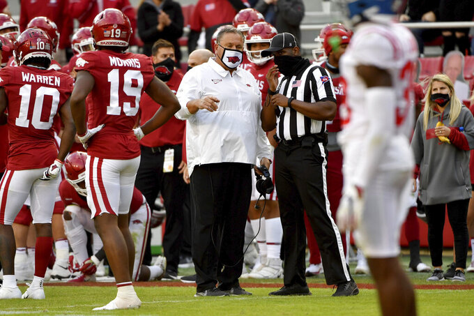 Arkansas coach Sam Pittman, center, talks with an official during the second half of an NCAA college football game against Mississippi, Saturday, Oct. 17, 2020, in Fayetteville, Ark. (AP Photo/Michael Woods)