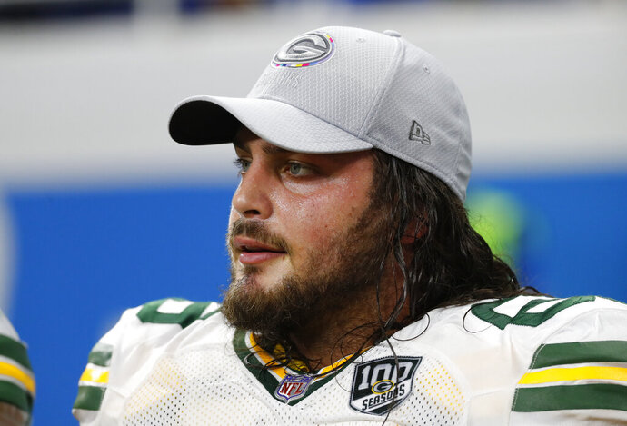FILE - In this Oct. 7, 2018 file photo, Green Bay Packers offensive tackle David Bakhtiari watches during an NFL football game against the Detroit Lions in Detroit.  Bakhtiari won't play Sunday, Oct. 25, 2020 against the Houston Texans due to a chest injury. The Pro Bowl lineman hadn't practiced all week and was listed as questionable in the team's Friday injury report.  (AP Photo/Paul Sancya, File)