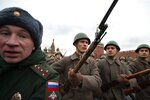 A Russian military police officer, left, escorts Russian soldiers dressed in Red Army World War II winter uniforms as they take a part in a reconstruction of a World War II-era parade in Moscow's Red Square, Russia, Thursday, Nov. 7, 2019. The Nov. 7, 1941 parade saw Red Army soldiers move directly to the front line in the Battle of Moscow, becoming a symbol of Soviet valor and tenacity in the face of overwhelming odds. (AP Photo/Alexander Zemlianichenko)