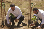Mexican Chancellor Marcelo Ebrard, left, and the El Salvador President Nayib Bukele plant trees during the launch of the