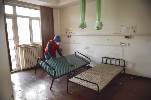 In this photo released by China's Xinhua News Agency, a worker moves a bed during renovations at the Xiaotangshan Hospital in Beijing, Thursday, Jan. 30, 2020. The hospital, which was used to quarantine patients during the SARS epidemic, is being renovated for possible use during China's current virus outbreak. (Peng Ziyang/Xinhua via AP)