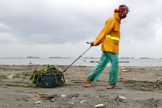 A worker wearing protective mask to prevent the spread of the new coronavirus pulls a plastic container full of debris washed ashore after tropical storm Saudel, locally called Pepito, hit the country on Wednesday, Oct. 21, 2020 in Manila, Philippines. The Philippine weather agency said Saudel continues to move out of the Philippines and is heading towards Vietnam. (AP Photo/Aaron Favila)