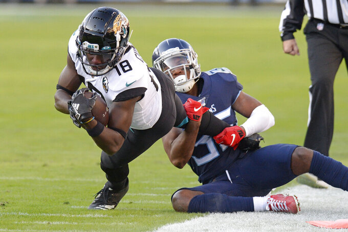 Jacksonville Jaguars wide receiver Chris Conley (18) is brought down by Tennessee Titans cornerback LeShaun Sims (36) in the first half of an NFL football game Sunday, Nov. 24, 2019, in Nashville, Tenn. (AP Photo/Mark Zaleski)