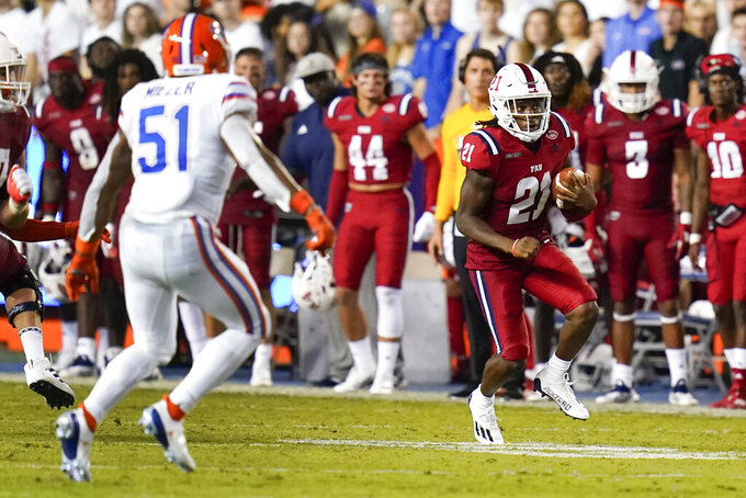 Florida Atlantic running back Kelvin Dean Jr. (21) looks for room to get around Florida linebacker Ventrell Miller (51) during the first half of an NCAA college football game Saturday, Sept. 4, 2021, in Gainesville, Fla. (AP Photo/John Raoux)