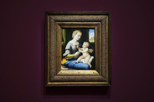 The painting 'Madonna of the Pinks' of Renaissance artist Raphael from London's National Gallery is on display at an exhibition at the Gemaeldegalerie in Berlin, Wednesday, Germany, Dec. 11, 2019. Berlin is opening the first of several Raphael exhibitions as the art world celebrates the 500th anniversary of his death next year. The show is dedicated to five famous Madonna paintings by the renowned Renaissance master that belong to Berlin's Gemaeldegalerie collections and another masterpiece of the Virgin Mary that is on loan from the National Gallery in London. (AP Photo/Markus Schreiber)