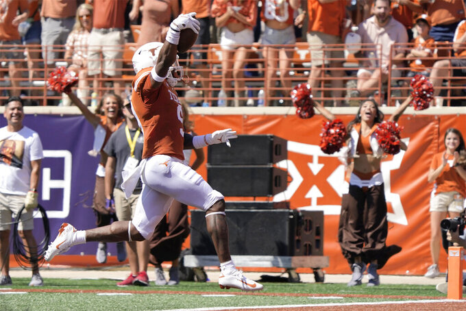 Texas defensive back Josh Thompson (9) celebrates as he returns an interception against Texas Tech for a touchdown during the first half of an NCAA college football game on Saturday, Sept. 25, 2021, in Austin, Texas. (AP Photo/Chuck Burton)