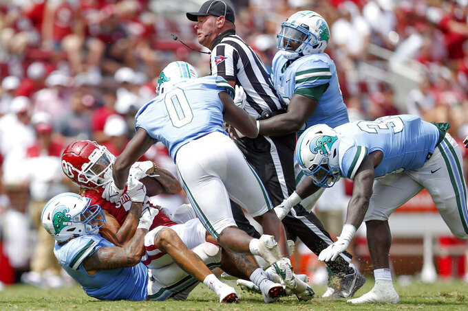 An official gets caught in a pile of player while Tulane defensive lineman Angelo Anderson (3) and linebacker Marvin Moody (0) tackle Oklahoma wide receiver Jadon Haselwood (11) during an NCAA college football game in Norman, Okla. on Saturday, Sept. 4, 2021. (Ian Maule/Tulsa World via AP)