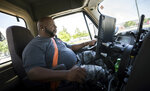 In this Wednesday, May 22, 2019 photo, Leon Brown drives his tractor-trailer on a delivery from a distribution center to the Port of Savannah,  in Garden City, Ga. Brown is trusted enough to drive a tractor-trailer inside one of the nation's busiest seaports more than six years after being released from prison. But he's not allowed to vote in Georgia because of a law rooted in the years after the Civil War when whites sought to keep blacks from the ballot box. (AP Photo/Stephen B. Morton)
