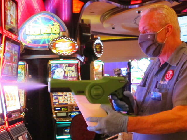 Steven Ford, a worker at Harrah's casino in Atlantic City, N.J., sprays slot machines with disinfectant Wednesday, July 1, 2020, as the casino prepared to reopen after 3 1/2 months of being shut down due to the coronavirus. Five of Atlantic City's casinos will reopen on Thursday, while three others, including Harrah's, will open Friday. (AP Photo/Wayne Parry)