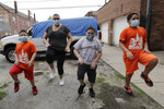 Mariana Ochoa, second from left, warms up with her children, Jesus, 5 , left, Victor, 7, second from right, and Mariano, 9, in front of their home in Chicago, Friday, May 22, 2020. Chicago Run's at-home fitness programs have become an essential part of the family's routine during the coronavirus pandemic. (AP Photo/Nam Y. Huh)