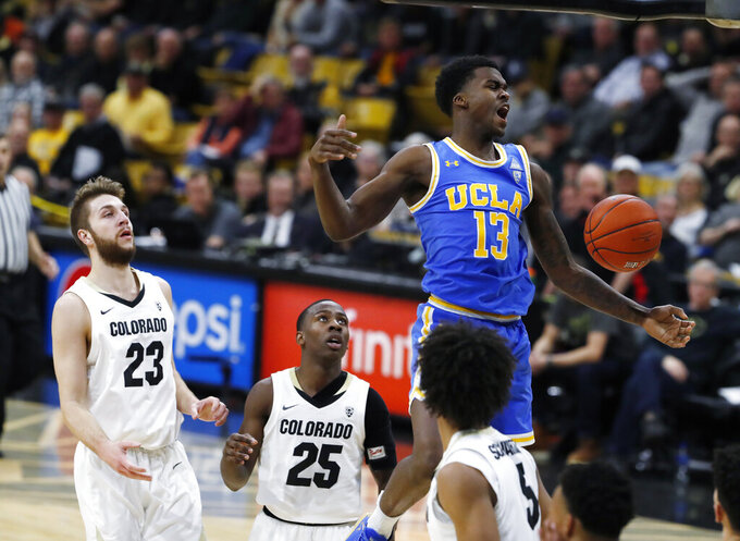 UCLA guard Kris Wilkes, third from left, reacts after dunking the ball for a basket as, from back left, Colorado forward Lucas Siewert and guard McKinley Wright IV look on with guard D'Shawn Schwartz, front, in the first half of an NCAA college basketball game Thursday, March 7, 2019, in Boulder, Colo. (AP Photo/David Zalubowski)