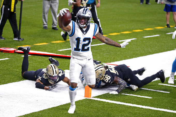 Carolina Panthers wide receiver D.J. Moore (12) crosses the goal line in front of New Orleans Saints free safety Marcus Williams (43) and outside linebacker Demario Davis (56) on a touchdown reception in the first half of an NFL football game in New Orleans, Sunday, Oct. 25, 2020. (AP Photo/Butch Dill)