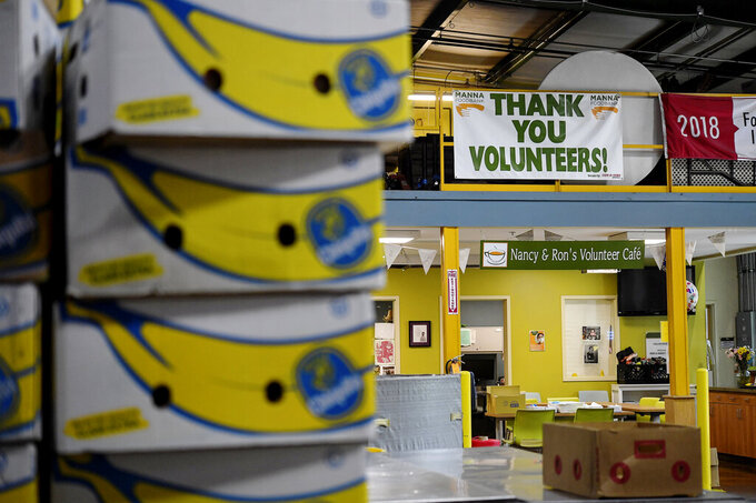 A sign thanking volunteers hangs above boxes of non-perishable food items at MANNA FoodBank's warehouse on Swannanoa River Road in Asheville, N.C., on Wednesday, May 5, 2021. The nonprofit and its partner agencies last March served 128,690 people in Western North Carolina, a 93% jump from February to the onset of the pandemic. (Angela Wilhelm /The Asheville Citizen-Times via AP)