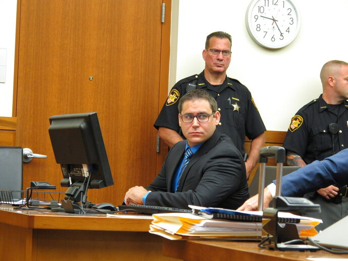 Former Ohio State diving club coach William Bohonyi, left, sits in court during his sentencing Monday, Aug. 12, 2019, in Columbus, Ohio. Bohonyi was accused of having sex with a teenage diver he coached and was sentenced to four years in prison after pleading guilty to sexual battery. (AP Photo/Kantele Franko)