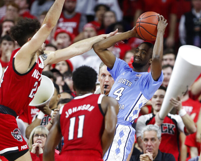 North Carolina's Brandon Robinson (4) looks to pass while pressured by North Carolina State's Devon Daniels (24) during the second half of an NCAA college basketball game at PNC Arena in Raleigh, N.C., Monday, Jan. 27, 2020. (Ethan Hyman/The News & Observer via AP)