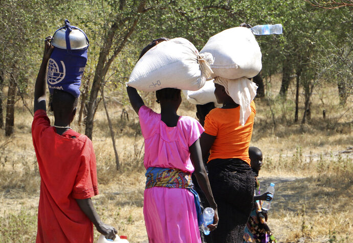 FILE - In this file photo taken Friday, Dec. 7, 2018, women and girls walk back after getting food in Bentiu, a 38 kilometers (24 miles) journey using a path through the bush for fear of being attacked on the main road, near Nhialdu in South Sudan. Brutal sexual violence committed with