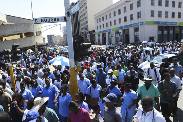 "FILE - In this Thursday Sept, 19, 2019 file photo, Zimbabwean medical staff march on the streets of Harare. A billionaire has offered to pay striking doctors in Zimbabwe to help end a months-long protest over grave hospital conditions as the economy crumbles, and a doctors' group on Thursday Jan. 23, 2020, said it was encouraging members to embrace the money and return to work. But Dr. Masimba Ndoro, vice president of the Zimbabwe Hospital Doctors Association, warned that ""nothing much has changed"" in the conditions at public hospitals that include the lack of basic items such as bandages and gloves. (AP Photo/Tsvangirayi Mukwazhi, File)"