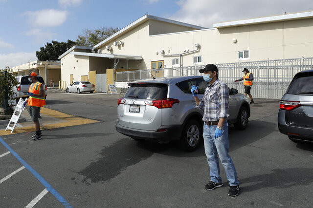 FILE - In this April 14, 2020, file photo, Radik Musin directs families in cars as they line up in San Diego to receive computers for San Diego Unified School District distance learning. California's second-largest school district announced stricter reopening guidelines than the state and officials say it will be months before students can return to campus. The San Diego Union-Tribune reported that the San Diego Unified School District will not reopen until there are fewer than seven community outbreaks over a week-long period. (AP Photo/Gregory Bull, File)