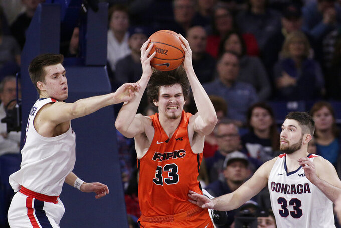 Pacific center James Hampshire, center, grabs a rebound between Gonzaga forwards Filip Petrusev, left, and Killian Tillie during the first half of an NCAA college basketball game in Spokane, Wash., Saturday, Jan. 25, 2020. (AP Photo/Young Kwak)