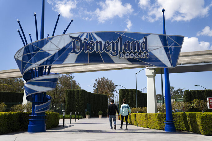 FILE - In this March 9, 2021, file photo, two visitors enter Disneyland Resort in Anaheim, Calif.  Disneyland announced Wednesday, March 17, that Disneyland and Disney California Adventure will reopen on April 30 with limited capacity. (AP Photo/Jae C. Hong, File)