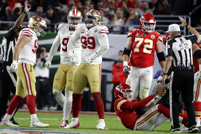 San Francisco 49ers' DeForest Buckner (99) celebrates after sacking Kansas City Chiefs quarterback Patrick Mahomes, bottom right, during the second half of the NFL Super Bowl 54 football game Sunday, Feb. 2, 2020, in Miami Gardens, Fla. (AP Photo/Wilfredo Lee)