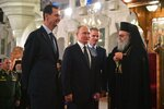 Russian President Vladimir Putin, center, Syrian President Bashar Assad, left, listen to Greek Orthodox Patriarch of Antioch and All the East, right, while visiting an orthodox cathedral for Christmas, in Damascus, Syria, Tuesday, Jan. 7, 2020. Putin has traveled to Syria to meet with President Bashar Assad, a key Iranian ally. The rare visit Tuesday comes amid soaring tensions between Iran and the United States following the U.S. drone strike last week that killed a top Iranian general who led forces supporting Assad in Syria's civil war. (Alexei Druzhinin, Sputnik, Kremlin Pool Photo via AP)
