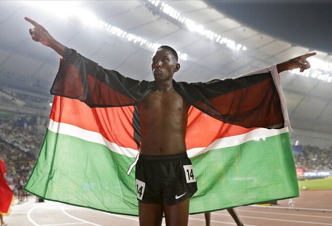 FILE - In this Friday, Oct. 4, 2019 file photo, Conseslus Kipruto of Kenya, gold medal winner in the the men's 3000 meter steeplechase final, celebrates at the World Athletics Championships in Doha, Qatar. Olympic steeplechase champion Conseslus Kipruto of Kenya has been charged with having sexual intercourse with a 15-year-old girl and was released on bail Monday, Nov. 16, 2020 after pleading not guilty. (AP Photo/Hassan Ammar, File)