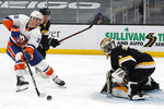 New York Islanders' Anthony Beauvillier reaches for the puck in front of Boston Bruins goaltender Jeremy Swayman during the second period of an NHL hockey game Friday, April 16, 2021, in Boston. (AP Photo/Winslow Townson)