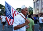 A protester holds an US flag during a rally in Tirana, Monday, July 8, 2019. Albania's opposition parties have resumed holding anti-government protests after their boycott of June 30 municipal elections. (AP Photo/Hektor Pustina)