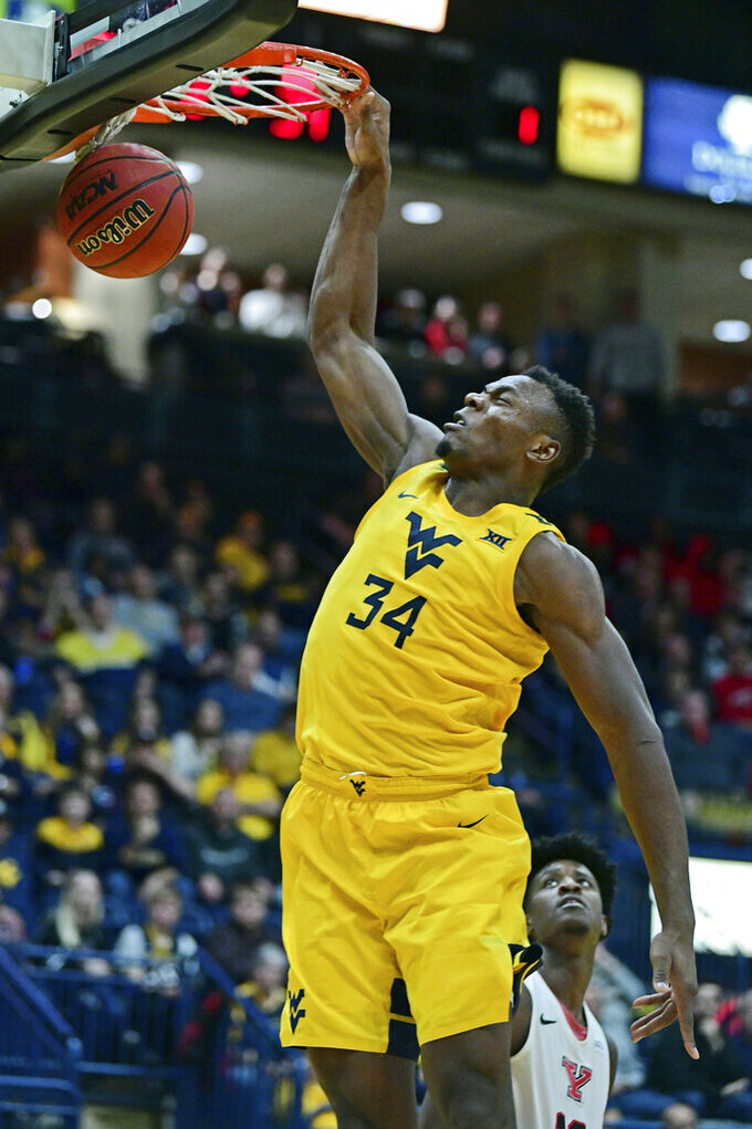 West Virginia forward Oscar Tshiebwe (34) dunks during the second half of an NCAA college basketball game against Youngstown State, Saturday, Dec. 21, 2019, in Youngstown, Ohio. West Virginia won 75-64. (AP Photo/David Dermer)