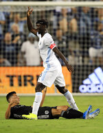 Minnesota United defender Ike Opara (3) steps over Sporting Kansas City forward Daniel Salloi during the first half of an MLS soccer match in Kansas City, Kan., Thursday, Aug. 22, 2019. (AP Photo/Orlin Wagner)