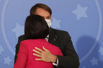Brazil's President Jair Bolsonaro cuddles his wife, Michelle Bolsonaro, during an event at the presidential palace in Brasilia, Brazil, Wednesday, July 29, 2020. According to an official statement released on Thursday the first lady has tested positive for COVID -19. (AP Photo/Eraldo Peres)