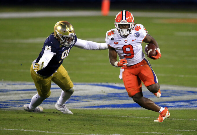 Clemson running back Travis Etienne (9) evades a tackle by Notre Dame defensive lineman Adetokunbo Ogundeji (91) as he runs for a touchdown during the first half of the Atlantic Coast Conference championship NCAA college football game, Saturday, Dec. 19, 2020, in Charlotte, N.C. (AP Photo/Brian Blanco)