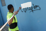 A man paints over the Spanish word