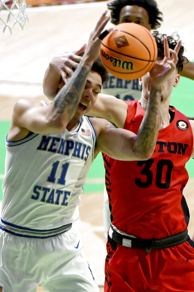 Memphis guard Lester Quinones (11) grabs a rebound in front of Dayton forward Mustapha Amzil (30) in the second half of an NCAA college basketball game in the first round of the NIT Tournament, Saturday, March 20, 2021, in Denton, Texas. Memphis won 71-60. (AP Photo/Matt Strasen)