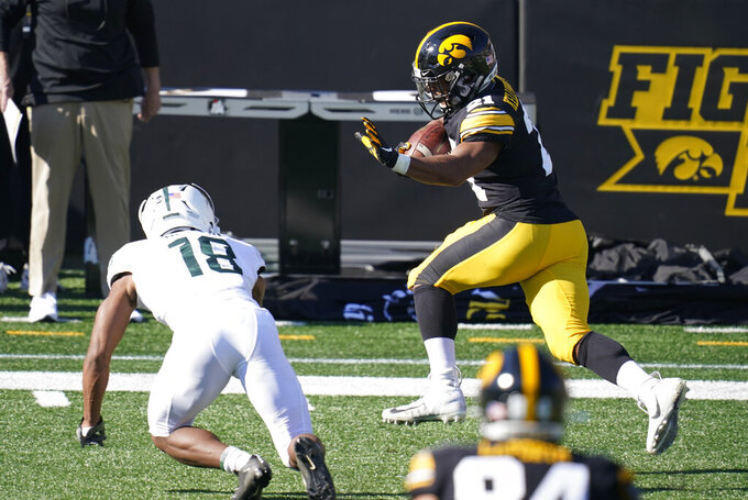 Iowa running back Ivory Kelly-Martin, right, runs from Michigan State cornerback Kalon Gervin (18) during the first half of an NCAA college football game, Saturday, Nov. 7, 2020, in Iowa City, Iowa. (AP Photo/Charlie Neibergall)