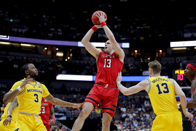 Texas Tech guard Matt Mooney shoots between Michigan guard Zavier Simpson, left, and forward Ignas Brazdeikis during the first half an NCAA men's college basketball tournament West Region semifinal Thursday, March 28, 2019, in Anaheim, Calif. (AP Photo/Jae C. Hong)