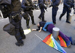 FILE - In this Saturday, March 23, 2019 file picture, anti-globalization activist Genevieve Legay, 73, lies unconscious after collapsing on the ground during a protest in Nice, southeastern France, as part of the 19th round of the yellow vests movement. Genevieve Legay was waving a rainbow flag marked