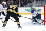 St. Louis Blues' Jordan Binnington (50) blocks a shot as Boston Bruins' Patrice Bergeron (37) looks for the rebound during the third period of an NHL hockey game in Boston, Saturday, Oct. 26, 2019. (AP Photo/Michael Dwyer)