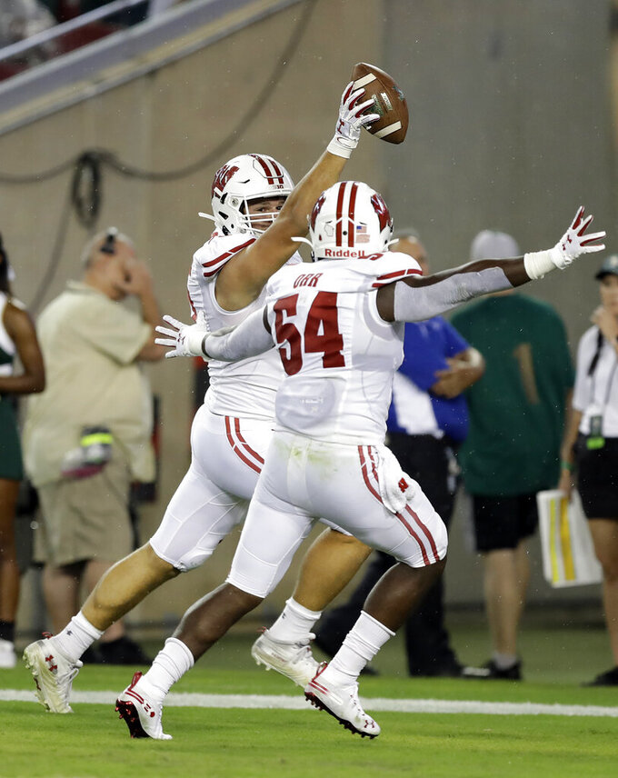 Wisconsin defensive end Matt Henningsen celebrates with linebacker Chris Orr (54) after Henningsen intercepted a South Florida pass and returned it for a touchdown during the first half of an NCAA college football game Friday, Aug. 30, 2019, in Tampa, Fla. (AP Photo/Chris O'Meara)