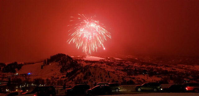 In this Saturday, Feb. 8, 2020 photo, a firework launched over Colorado ski resort town of Steamboat Springs explodes Saturday, Feb. 8, 2020. The firework has set a record as the world's largest aerial firework. The 2,800-pound shell flew 2,200 feet above the Steamboat Springs Winter Carnival before it burst on Saturday night. Guinness World Records representatives witnessed and certified the record.  (AP Photo/Steve Caulk)