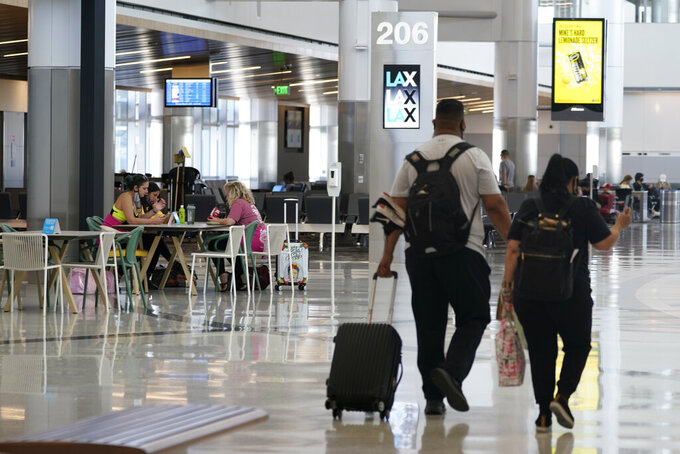 Passengers wait for their flights inside the new West Gates at Tom Bradley International Terminal at Los Angeles International Airport Monday, May 24, 2021, in Los Angeles. (AP Photo/Ashley Landis)
