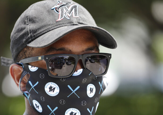 A line of cars is reflected in the sunglasses of Evans Adonis, Director, Membership Sales for the Miami Marlins baseball team at a food and mask distribution site put on by the Miami Marlins baseball organization, Monday, June 29, 2020, outside Marlins Park stadium in Miami. (AP Photo/Wilfredo Lee)
